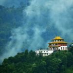 Monastery in Sikkim surrounded by lush greenery and fog